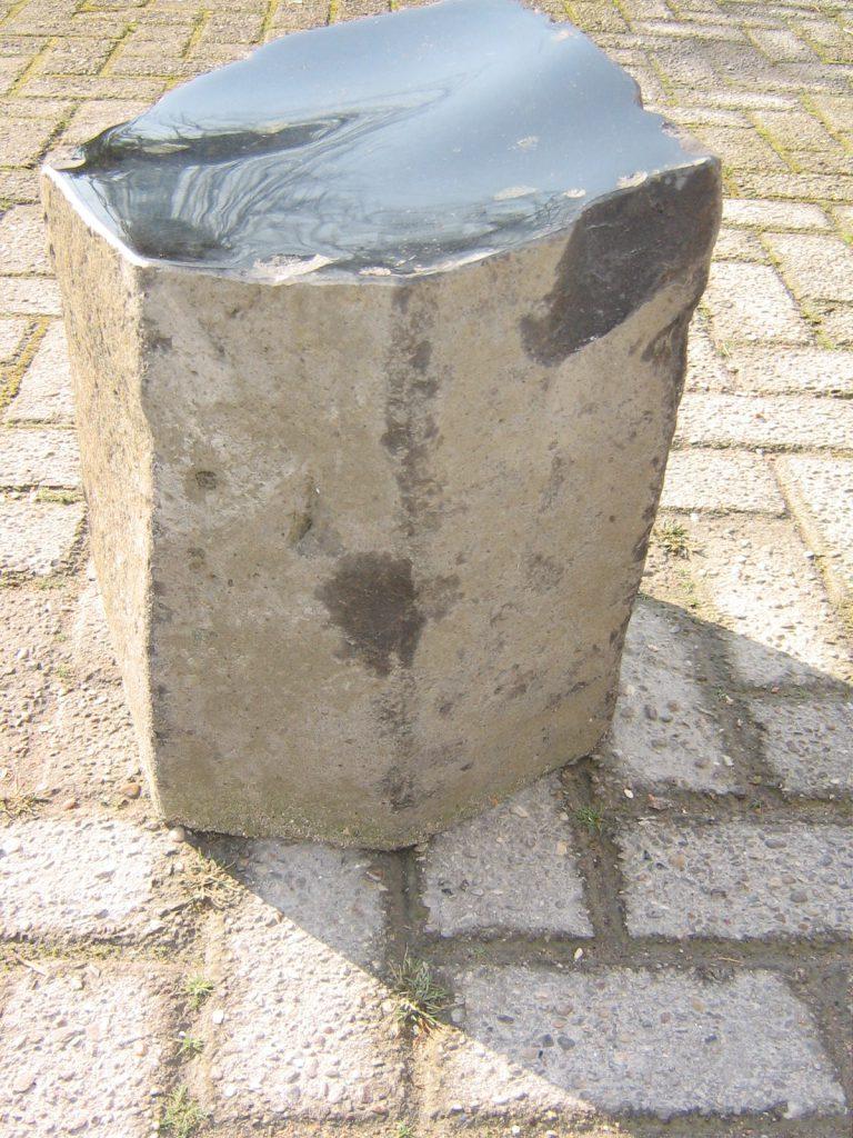 """Titel: """"Basalto uno"""", Zetel voor op grafmonument of tuin. Materiaal: basalt. Herkomst: Duitsland. Bewerking: gepolijst afwaterend zit vlak. Formaat: 30 x 30 x 37 cm. Ontwerp: Niek Wittebrood, Copyright 2008."""