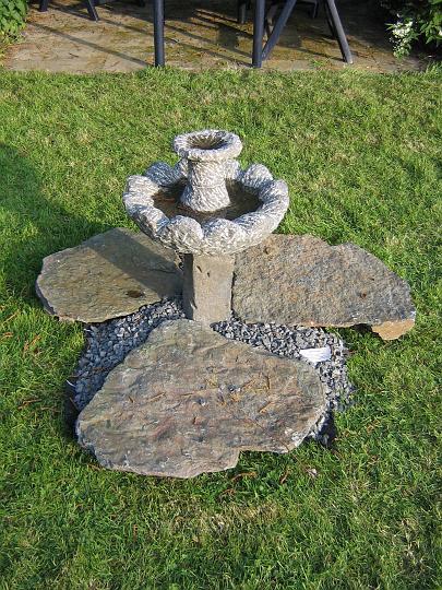 Deze kleine versie van de Lotus fontein is hier opgesteld als water schaal met flagstones Violetta, Luxemburgse leisteen als plompe bladeren. Formaat: diameter 40 x 50 cm hoog totale diameter ca. 90-100 cm. Materiaal: Belgisch Hardsteen, basalt zuil.