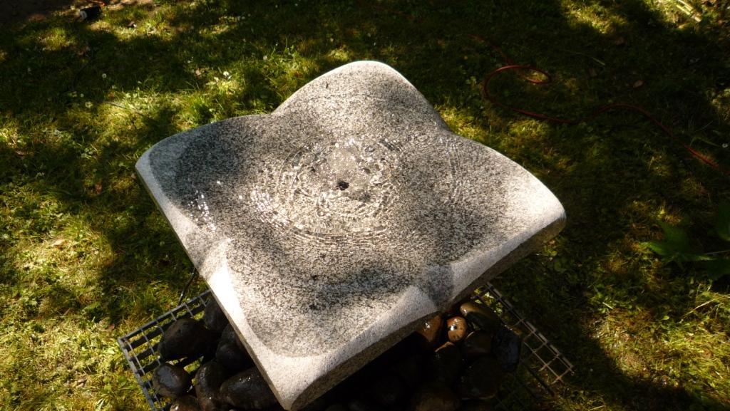 Hier zie je de cirkelvormige waterstroom waarmee het water kabbelt over deze steenbloem van graniet. De bodem is gepolijst en makkelijk schoon te houden. Een perfecte bad en drinkplaats voor volgels waar het stromende water levend blijft.