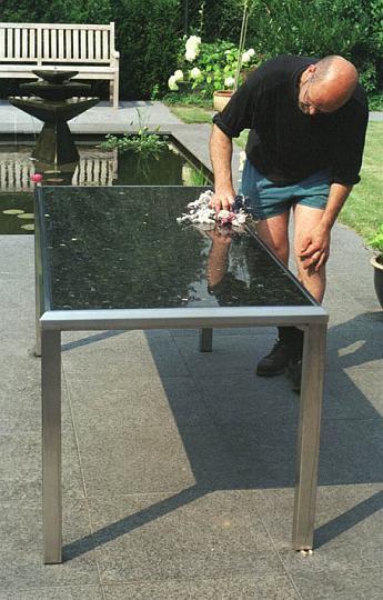 Speciaal ontworpen frame in r.v.s. voor deze tuintafel, De steen ligt als een sieraad in het frame, strak en gepolijst. Een genot om aan te eten in de schaduw, zon of beschut voor de regen. Makkelijk te onderhouden super duurzaam. Formaat 150 x 75 x 72 cm. Materiaal: r.v.s. Labrador Donker gepolijst. Andere materialen en kleuren op aanvraag.