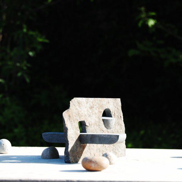 """Dit ontwerp is speciaal voor de beweegtuin van """"De Plataan"""" Zorgcentrum in het Soester kwartier, ontworpen. op schaal 1:10 in de originele materiaal en bewerking. Een zijde is nog de ruwe steen zoals deze uit de berg kwam, de andere zijde is gepolijst en kan met lijnen en reliëf worden betekent. In de plaat is een rond en een rechthoekig gat gemaakt waarin respectievelijk een schaal en een bewegende wip is gestoken. rondom het object zijn zit en beweeg keien geformeerd in een cirkel. in, op en aan het object kan water een functie hebben. Het ontwerp is verder nog niet in detail uitgewerkt."""