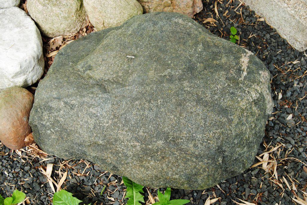 Deze Gabbro zwerfkei is wat platter en heeft wat meer reliëf. Deze kei is geschikt voor een kleine tekst met een enkele naam en datum. handmatig gehakt, gezandstraalde of bronsletters of een mooie bronsplaat in de steen verzonken. Maat: ca. 75 x 45 x 25 cm. De steen kan ook schuin liggend, op z'n zijkant of staand rechtop worden geplaatst.
